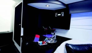 The small wetbar has a Corian countertop, stainless steel sink and refrigerator with the stereo located just above.